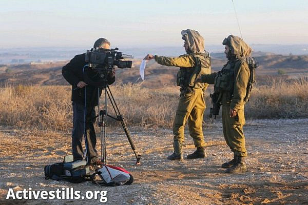 Israeli soldiers show an order for a closed military zone to a cameraman on the Israeli side of the border with Gaza, November 15, 2012. (by: Oren Ziv/Activesillts.org)