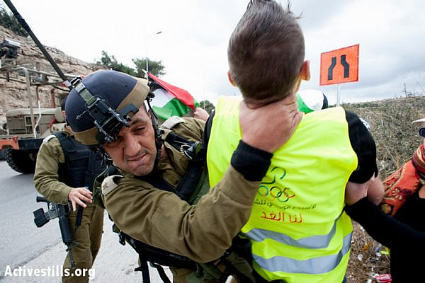 An Israeli soldier grabs an international activist by the neck while attempting to make an arrest, Al Nashash Junction, November 14, 2012. The activists intended to block traffic on Route 60, the main north-south highway in the West Bank. (photo: Ryan Rodrick Beiler/Activestills.org)