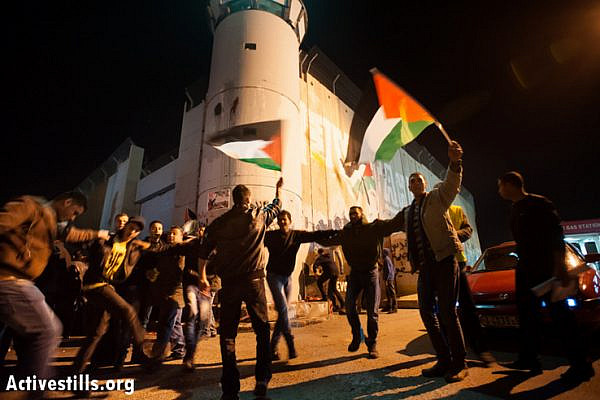 "Palestinians dance in front of the Israeli separation wall in the West Bank town of Bethlehem in anticipation of the Palestinian bid for ""nonmember observer state"" status at the United Nations, November 29, 2012. Hours later, the UN General Assembly voted 138-9 in favor of the upgraded status for Palestine, with 41 nations abstaining. (Photo by: Ryan Rodrick Beiler/Activestills.org)"