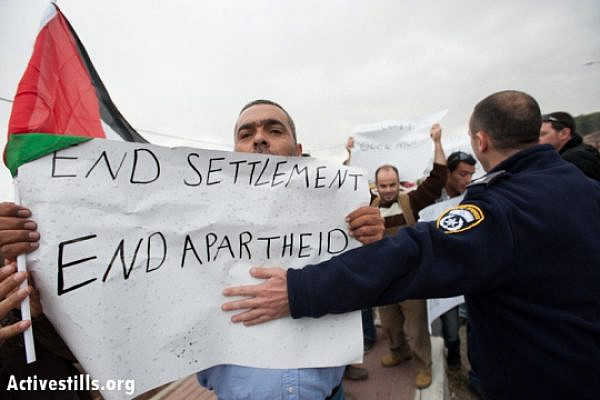 An Israeli policeman attempts to control Palestinian activists demonstrating against the occupation, Gush Etzion junction, November 9, 2012.