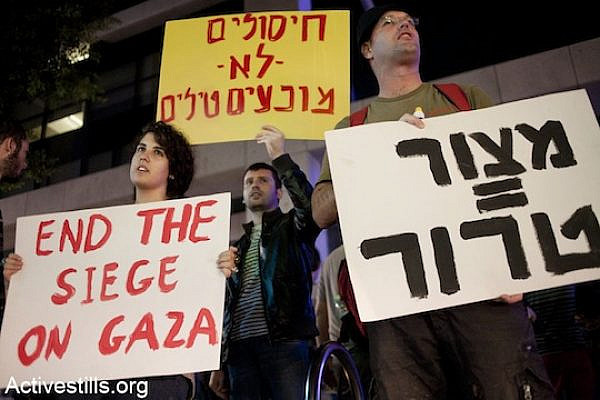 """Israelis protest in front of the Tel Aviv residence of the Israeli Minister of Defense, Ehud Barak, against the attack on Gaza on, Tel-Aviv, November 14, 2012. The signs read (from R to L): """"Siege=Terror"""" and """"assassinations don't prevent missiles."""" (photo: Keren Manor/Activestills.org)"""