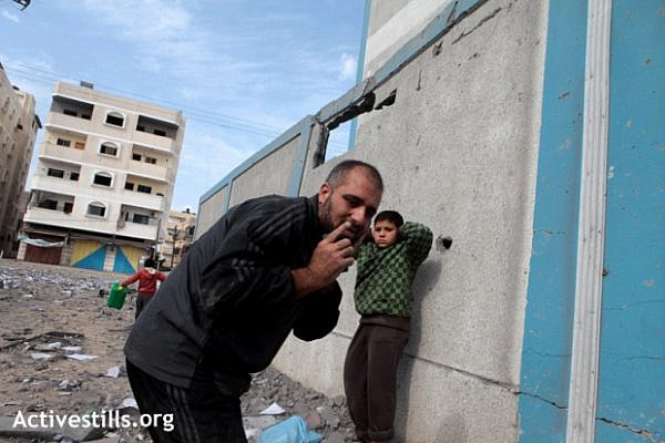A Palestinian man and boy react to the sound of a Israeli warplane, flying at very low altitude above the ruins of the government building, which was completely destroyed that morning. Gaza city, November 17, 2012 (photo: Anne Paq/Activestills.org)