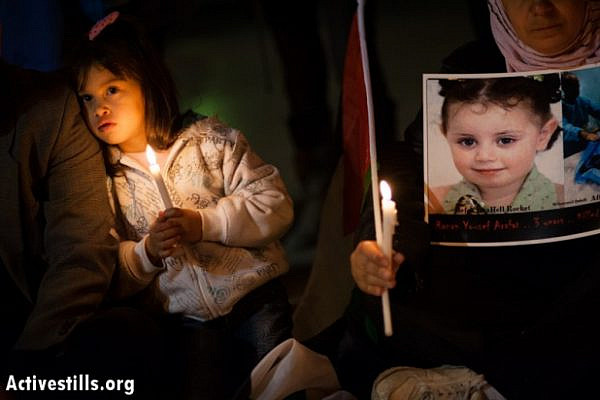 A girl holds a candle next to a photo of 3-year-old Ranan Yousef Arafat, who was killed by Israeli airstrikes in Gaza, as Palestinians gathered in Bethlehem's Manger Square to mourn the victims of Israeli military strikes and to call for an end to the escalation of violence, November 17, 2012 (photo: Ryan Rodrick Beiler/Activestills.org)