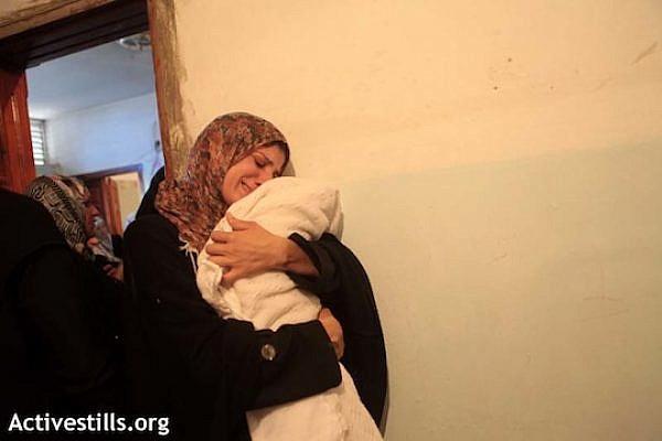 The mother Matar Abu Al-Atta, holding her newborn baby, born the night Matar was killed. (photo: Anne Paq / Activestills)