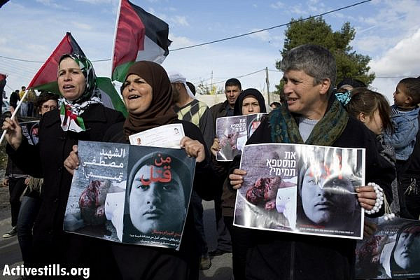 "Palestinian and Israeli activists hold a poster asking ""Who Killed Mustafa Tamimi?"" during the weekly protest against the occupation in the West Bank village of Nabi Saleh, December 7, 2012. Tamimi was killed on December 9, 2011, when he was shot in the face with a tear gas canister at close range by Israeli soldiers. Also pictured on the poster is soldier who killed Tamimi. No one responsible for Tamimi's death has been brought to justice to this day. (photo by: Oren Ziv/ Activestills.org)"