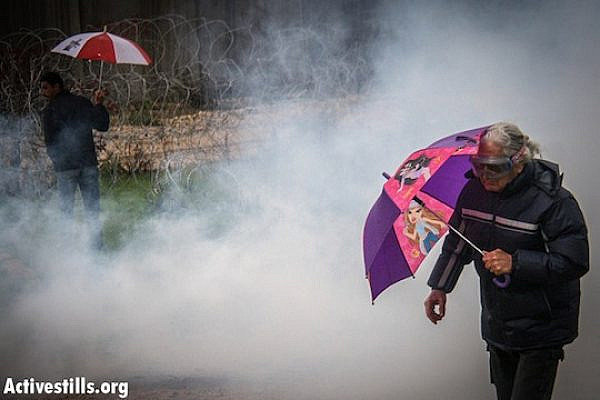 Demonstrators walk inside a cloud of tear gas shot by the Israeli army during the weekly protest against the wall and the occupation in the West Bank village of Bil'in, December 21, 2012. (photo by: Guest photographer Hamde Abu Rahma/ Activestills.org)