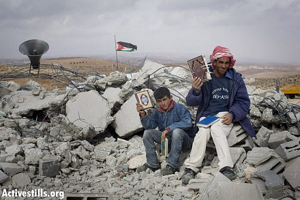 Fadel hammadi and his son, Abed, hold copies of the Koran as they sit on top of a mosque that was demolished by Israeli forces in the West Bank village of al-Mufaqara, south of Hebron, on December 4, 2012. (photo by: Oren Ziv/ Activestills.org)