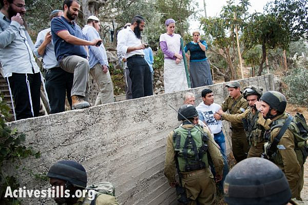 With Israelis from Tel Rumeida settlement looking on from above, Israeli soldiers arrest two Palestinians and an international volunteer after confrontations between settlers, the Al Azzeh family who had just harvested their olives, and the military, October 22, 2012. The arrests followed the first time the Al Azzeh family was able to harvest their olives since 2007. Despite coordinating with the appropriate authorities, their harvest was disrupted by Israelis from the adjacent Tel Rumeida settlement, which like all settlements, is illegal under international law. (photo: Activestills)