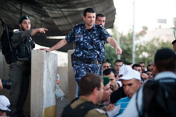 Palestinian Authority police (right) together with Israeli border police (left) control Palestinian access to Jerusalem, at the Bethlehem checkpoint on the last Friday of Ramadan, August 17, 2012.  This Ramadan, Israeli authorities only allowed males under 12 or over 40 access without a special permit;  females of all ages were allowed to pass freely.