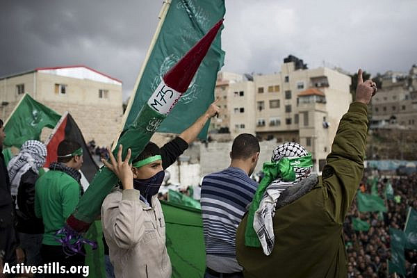 A Palestinian youth holds a mock rocket as thousands of Palestinians celebrate Hamas' 25th anniversary in the West Bank city of Hebron, December 14, 2012. This is the first time since 2007 that the Palestinian Authority has allowed Hamas to celebrate its anniversary in the West Bank. (photo by: Oren Ziv/ Activestills.org)