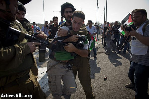 Israeli soldiers try to arrest Activestills photographer Yotam Ronen, as Palestinian and international activists block 443 highway, which connects Tel Aviv and Jerusalem through the West Bank, during a protest against the violence of  the Israeli settlers, October 16, 2012.