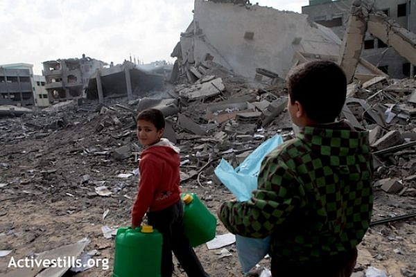 Children walk by the ruins of the Ministry of Interior's Civil Department building, completely destroyed that morning, in the Tal el Hawa neighbourhood, Gaza city, November 17, 2012. The death toll in the Gaza Strip rose to 41 on Saturday, with hundreds more injured on the fourth day of a massive Israeli military attack on the Gaza Strip. Dozens of civilian and governmental facilities have been also destroyed. (Photo by: Anne Paq/Activestills.org)