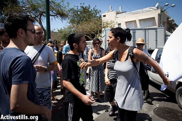Arsonist-assister Haim Mula (center) confronting anti-racism activist (Oren Ziv / Activestills)