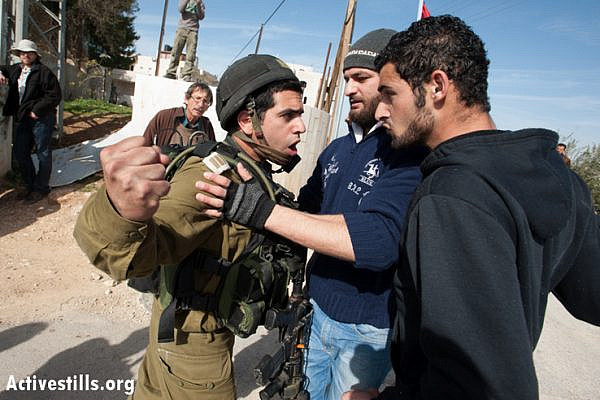 An Israeli soldier threatens to punch a Palestinian activist during a weekly nonviolent demonstration against the Israeli separation barrier, Al Ma'sara, West Bank, January 18, 2013. If completed as planned, the wall would cut off the village from its agricultural lands. (Photo by: Ryan Rodrick Beiler/Activestills.org)