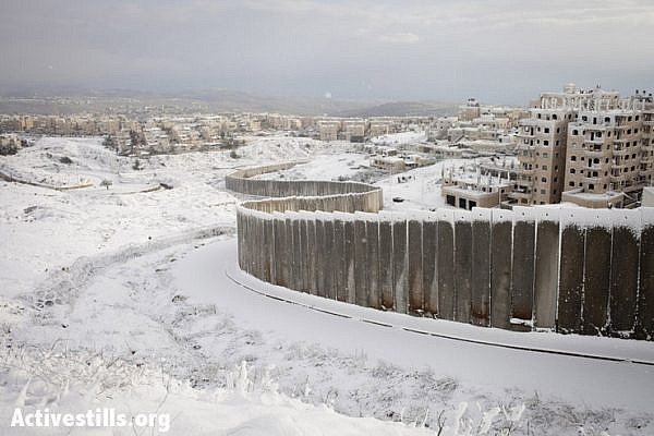 The Separation Wall between Shu'fat and Pisgat Zeev settlement, seen covered with snow after a winter storm, January 10, 2013. (Photo by: Shiraz Grinbaum/Activestills.org)