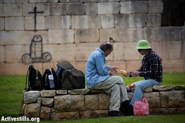 Israeli couple picnics near offensive graffiti in Bir'em (Oren Ziv / Activestills)