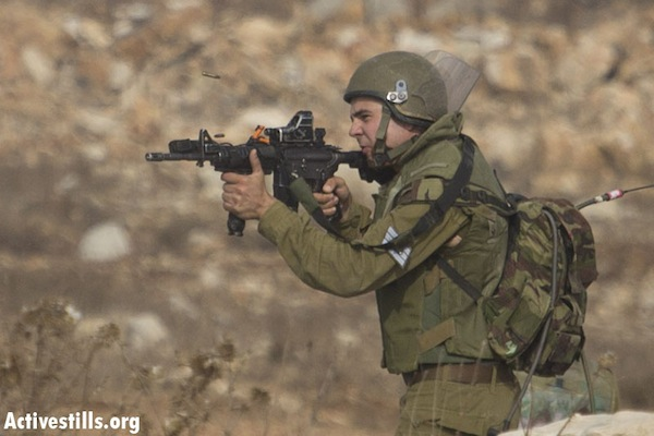 IDF soldier shooting live bullets at demonstrators in Nabi Saleh, November 2, 2012 [illustrative] (Photo: Oren Ziv/Activestills.org)
