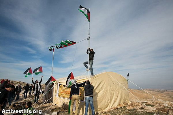 Activists raise the Palestinian flag over the Bab AlShams, reclaiming a Palestinian privately owned hilltop in the E1 area of the West Bank, currently slated for settlement by Israeli authorities.