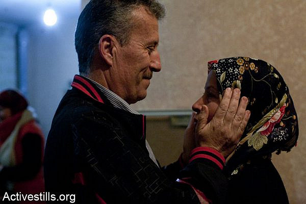 Released political prisoner Bassem Tamimi hugs his wife Neriman during his welcoming party at his home in Nabi Saleh, after spending three months in an Israeli jail, February 10, 2013.  Tamimi was arrested during an action calling for the boycott of settlement products inside an Israeli supermarket located in the West Bank settlement of Geva Binyamin. (Photo by: Keren Manor/ Activestills.org)
