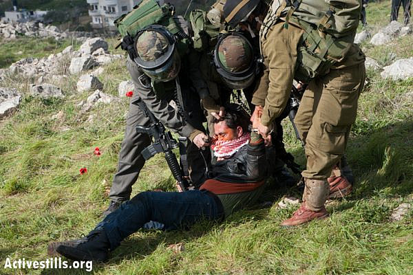 An Israeli soldier pepper sprays a restrained Palestinian activist at point blank range in a newly created protest village named Al Manatir on land belonging to the West Bank village of Burin, February 2, 2013. (Photo by: Ryan Rodrick Beiler/Activestills.org)