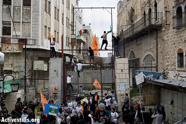 Demonstrators climb on a fence, built by the Israeli army to close Shuhada Street to Palestinians, in the West Bank city of Hebron February 22, 2013. (Photo by: Oren Ziv/Activestills.org)