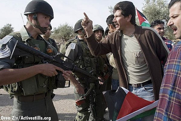 Adeeb Abu Rahme, one of the residents of Bil'in who appears in 5 Broken Cameras, confronts the IDF during a protest in 2007 (Activestills)