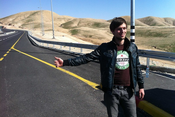 A hitchhiker outside the West Bank settlement of Kfar Adumim [illustrative] (Craig Antweiler / CC)