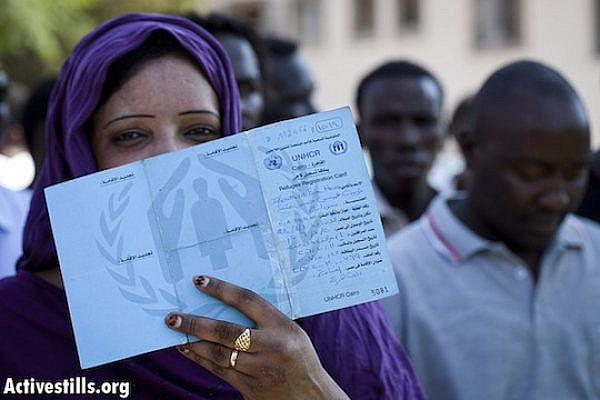 A Sudanese woman shows her UNHCR Refugee card from Egypt during a refugee protest in front of the government's offices in center Tel Aviv October 14, 2012. (photo: Oren Ziv/Activestills)