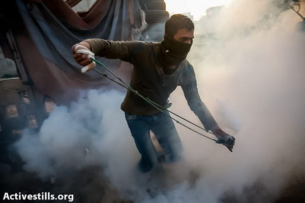 A youth throwing back a gas canister shot by israeli soilders in the West Bank village of  Nil'in on March 1, 2013, during a demonstration against the occupation. (Photo by: Yotam Ronen/Activestills.org)