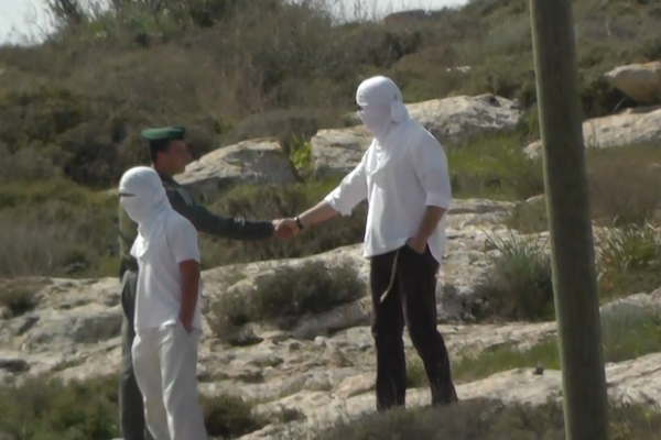 Border Police officer shaking hands with masked Israeli settler, March 2, 2013 (Guy, Ta'ayush activist)