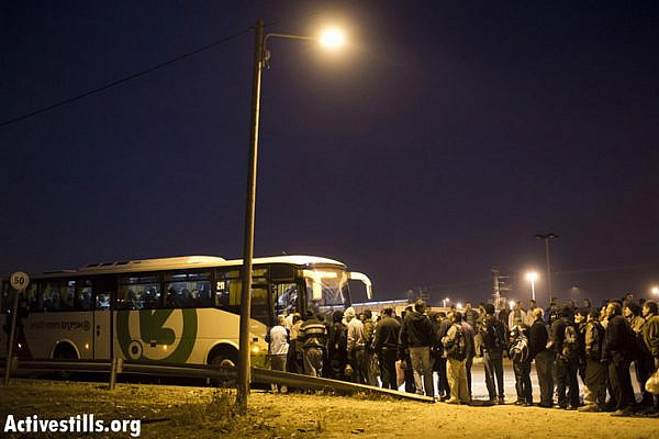 Palestinian workers wait in line to board an Israeli bus line meant for Palestinians only after crossing the Eyal checkpoint from the West Bank into Israel proper. (Photo by Activestills.org)