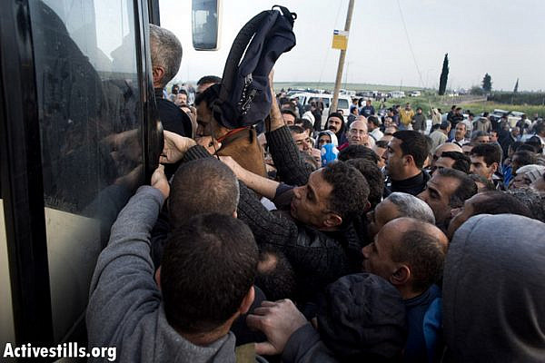 Palestinian workers board a new segregated bus line at the Eyal checkpoint, March 4, 2012.