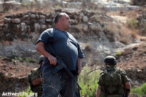 An armed settler stands with IDF troops near Nabi Saleh [illustrative photo], 19.09.2011 (Anne Paq/Activestills.org)