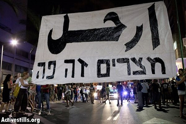 "Israeli social protest activists in the summer of 2011 hold a banner emblazoned with the Arabic word ""erhal"" - leave. Below, the line in Hebrew reads, ""Egypt is here."" (credit: Oren Ziv/Activestills)"