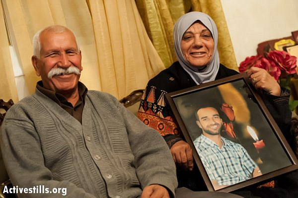Tareq and Layla Issawi, the father and mother of Palestinian hunger striker Samer Issawi, smile with a portrait of their son in their home in the East Jerusalem neighborhood of Issawiya, two days after he signed an agreement with Israeli authorities to end his strike, April 24, 2013. Under the terms of the agreement reached late Monday, April 22, Issawi will be released to his hometown of Jerusalem after serving eight more months in jail, after 266 days of refusing food in protest against his rearrest by Israeli forces after being released in the Gilad Shalit prisoner exchange in October 2011. (Photo by: Ryan Rodrick Beiler/Activestills.org)