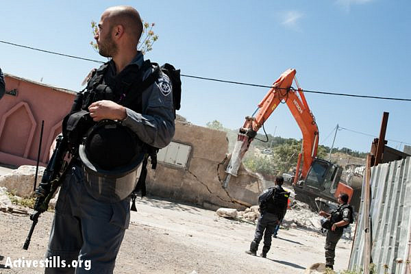 Israeli border police guard for the demolition of the Jaradat family home in the Al Tur neighborhood of East Jerusalem, April 24, 2013. (photo: Ryan Rodrick Beiler/Activestills.org)