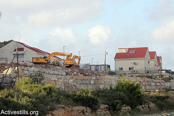 Israeli bulldozers seen in the settlement of Halamish showing the continued building and expansion of the settlement on the lands of the West Bank village of Nabi Saleh, April 19, 2013. (Photo by: Ahmad Al-Bazz/Activestills.org)