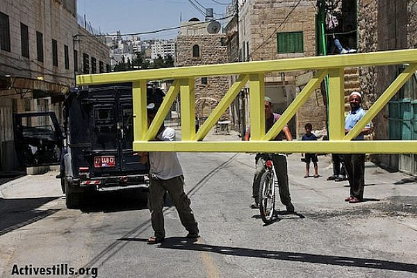 Jewish settlers close a gate blocking access to Shuhada Street in Hebron (Anne Paq/Activestills.org)