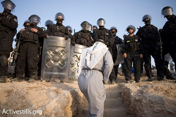 A resident of al-Araqib approaches Israeli police during one of the dozens of times authorities demolished the unrecognized village. (Activestills.org)