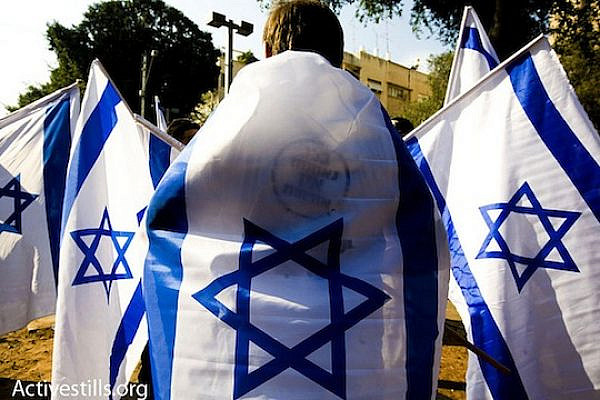 A right wing protester holds up Israeli flags while thousands march in the annual human rights march in Tel Aviv. Photo by Activestills.org