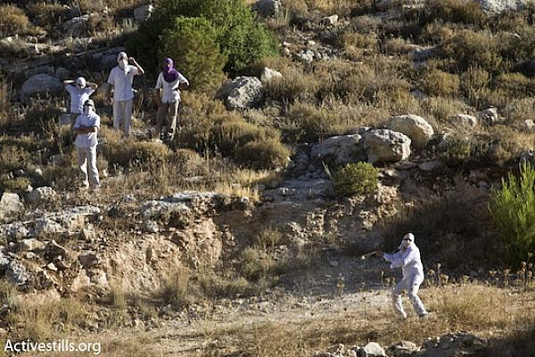 A masked Jewish settler uses a slingshot to throw stones at Palestinians [illustrative photo] (Oren Ziv/Activestills.org)