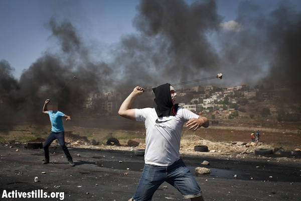 Palestinian youth throw stones near Ofer Military Prison [illustrative], May 15, 2012 (Oren Ziv/Activestills.org)