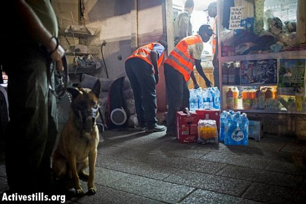 Policeman and attack dog watch over African workers emptying asylum seeker's store (Oren Ziv / Activestills)