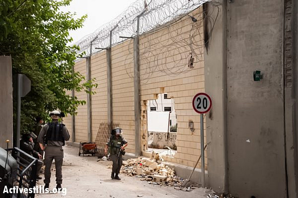 Israeli border police guard the Separation Wall between the East Jerusalem neighborhood of Ras Al 'Amud and the West Bank town of Abu Dis, May 19, 2013, after Palestinian protesters broke a large hole through it during a demonstration two days previous. (Photo by: Ryan Rodrick Beiler/Activestills.org)