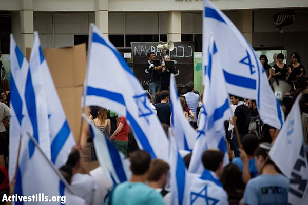 Right-wing protesters wave Israeli flags as they demonstrate against a ceremony commemorating the Nakba that was held by Palestinian and Israeli students in the entrance to the Tel Aviv University. The event took place under heavy police presence, May 13, 2013. (Photo by: Oren Ziv/Activestills.org)