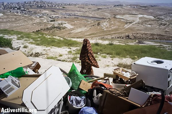 A member of the Palestinian Ghaith family stands with the belongings of her family after her house was demolished by Jerusalem municipality workers in the East Jerusalem neighborhood of At-Tur on April 29, 2013. (Tali Mayer/ Activestills.org)
