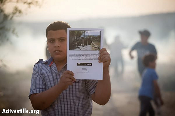 A Palestinian youth in Budrus, with his new copy of the graphic novel, after the Israeli army interrupted the event, shooting tear gas into the village.