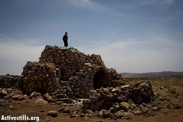 A Palestinian man stands on top of a stone structure, used by Palestinian farmers of the area, which Israeli settlers took over a few weeks ago, in the West Bank village of Deir Jarir, May 23, 2013. (Photo by: Oren Ziv/ Activestills.org)