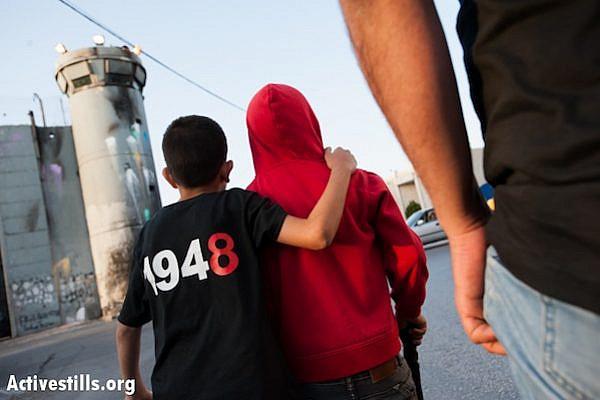 Palestinians march through the streets of Bethlehem to commemorate the Nakba, May 14, 2013. (Ryan Rodrick Beiler/Activestills.org)