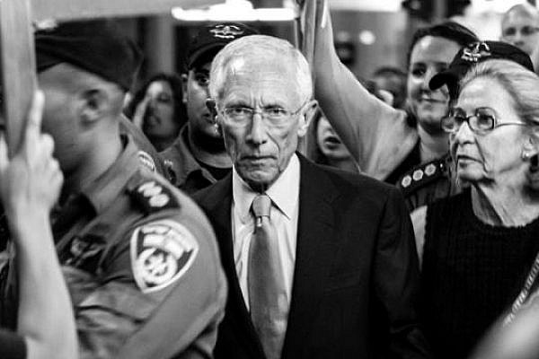 The Governor of the Bank of Israel and former Chief Economist World Bank Stanley Fischer surrounded by protesters as they walk out of a cultural event in Tel Aviv, May 25 2013 (photo: Ilai Ben Amar)